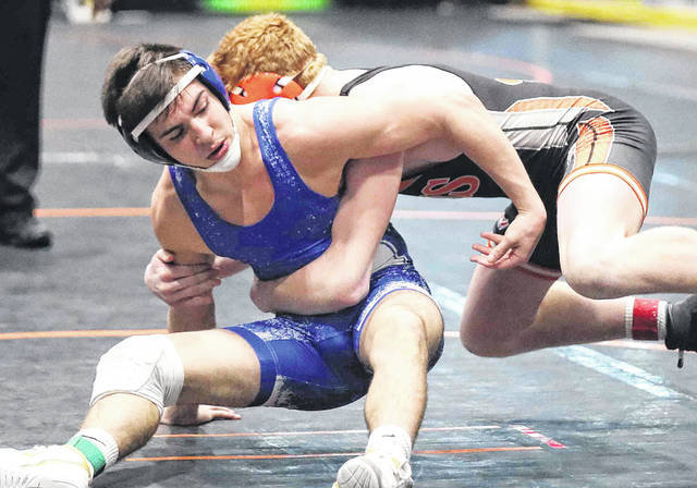 Allen East's Kade Wireman attempts to get out of the hold of Versailles' Caron Bey during Saturday's Division III district at Hobart Arena in Troy.