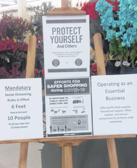 """Hobby Lobby has signs indicating people should take precautions during new coronavirus pandemic. Hobby Lobby on Elida Road reopened Monday after corporate officials decided it was an """"essential"""" business."""