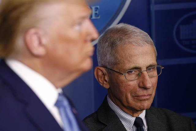 Director of the National Institute of Allergy and Infectious Diseases Dr. Anthony Fauci, right, and President Donald Trump listen as Vice President Mike Pence speaks during a coronavirus task force briefing at the White House on Saturday. (AP Photo/Patrick Semansky)
