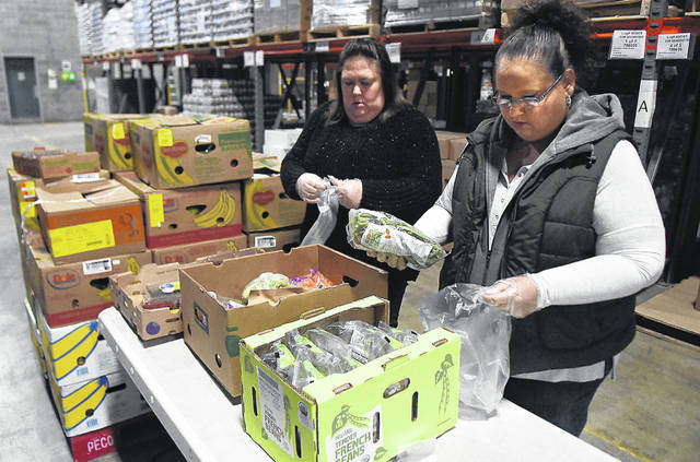 Ginger Loscavo, left, and Tommie Harner pack emergency pantry bags of food and vegetables at the West Ohio Food Bank to be distributed over the weekend. The West Ohio Food Bank is one of the larger standard nonprofits in the region. Covering 11 counties with annual revenue nearing $9 million, the staff only numbers 13.