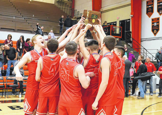 Columbus Grove players hold up the Division IV district championship trophy they won Friday night at the Elida Fieldhouse.
