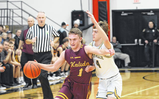 Kalida's Ayden Warnecke drives against Ottoville's Kyle Manns during a Tuesday night Division IV district semifinal at the Elida Fieldhouse.