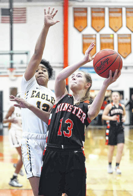 Minster's Janae Hoying, here putting up a shot against Toledo Christian's Cat Jones during a Division IV regional semifinal last week at the Elida Fieldhouse, is averaging 12.5 points and 2.5 assists per game.
