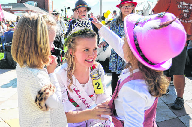 Four year-old Alli Wiss (left) and four year old Ivy Quinter check out Miss Oktoberfest Madison Wiss's crown during the Minster Oktoberfest on Saturday afternoon.  Amanda Wilson -The Lima News