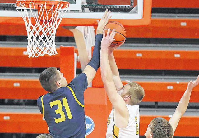 Ottawa-Glandorf's Ben Westrick defends a shot by Colonel Crawford's Reis Walker during a Wednesday night Division III regional semifinal at the Stroh Center in Bowling Green.
