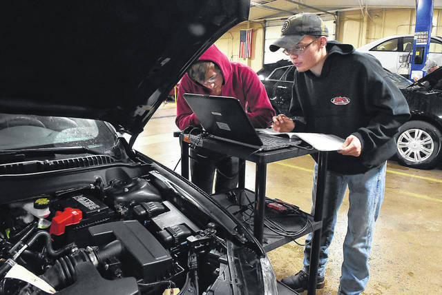 P.J. Childs and Kevin Gibney perform a computerized diagnostic test on a vehicle during class at University of Northwestern Ohio. Craig J. Orosz | The Lima News