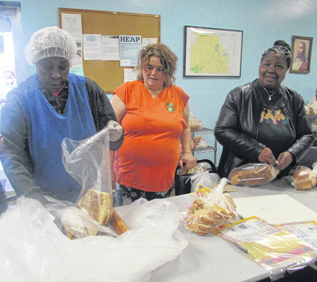 At Our Daily Bread soup kitchen in Lima, volunteers Brenda Williams, from left, Rosa Gmoon and Vernice Koger get food ready to distribute.