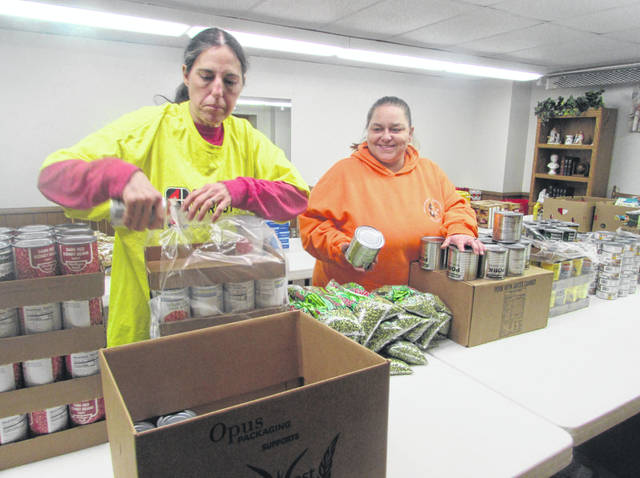 Sue Ann Chafin, left, and Jessie Roark, Lima St. Mark's Church Resource Center volunteers, pack boxes of canned goods to distribute to the community.
