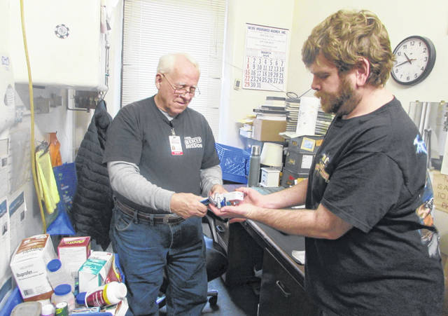 James McGuire, Lima Rescue Mission staff mamber, left, gives hygiene items to resident Michael Adkins.