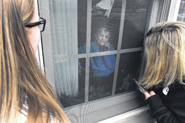 Standing outside communicating with cell phones, Chloie Bennett, 14, and her mother, Wendy, visit with her grandmother, Stella Goodwin, 87, at Burton's Ridge in Shawnee Township on Thursday. Craig J. Orosz | The Lima News