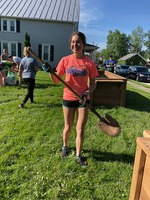 Taylor Paul, center, works with volunteers and family to plant vegetables in the Golden Harvest Community Orchard, which Paul founded in 2019 as part of a Girl Scout project.