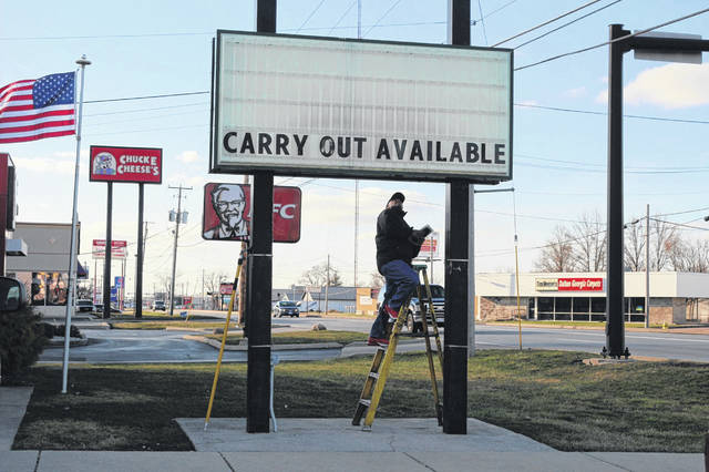 A worker changes the marquee Sunday at Western Sizzlin on Elida Road in Lima shortly after Gov. Mike DeWine closed inside dining at bars and restaurants across the state.