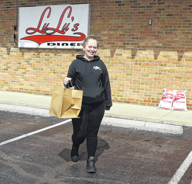 Jenea Johnston picks up some food at Lulu's Diner on Lima's Spencerville Road on Sunday. All dine-in restaurants in Ohio have had to prohibit people from eating inside their establishments since March 15 due to the COVID-19 virus.