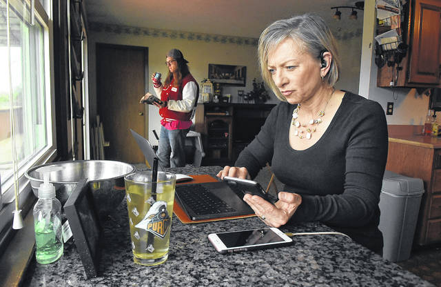 Bobbie Glon, a health coach mentor and clinical specialist, works on her laptop while sitting in her kitchen. On the left is her son, Harrison Stechschulte, 18, a senior at Bluffton High School who is home during the school shutdown due to the coronavirus.