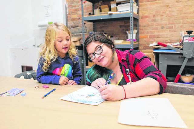 "Maia Fisher, of Wapakoneta, teaches 5-year-old Harper Devita, of Lima, how to draw animations during a ""create your own superhero"" workshop held in the past at ArtSpace/Lima."
