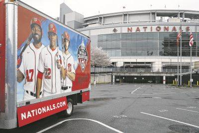 A truck sits in the players parking lot Wednesday at Nationals Park in Washington. With the start of the Major League Baseball season indefinitely on hold because of the novel coronavirus pandemic, ballparks will be empty today on what was supposed to be opening day.