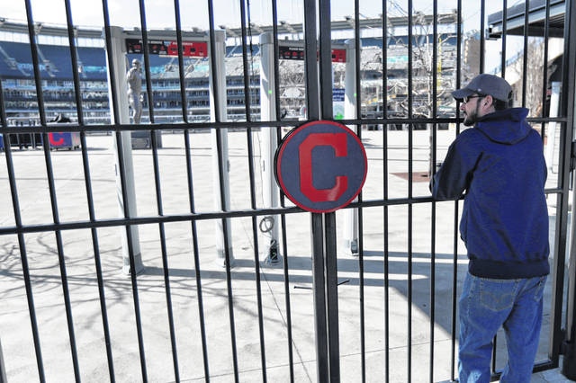 Jason Hackedorn looks into Progressive Field, home of the Cleveland Indians baseball team Thursday, March 26, 2020, in Cleveland. With the start of the Major League Baseball season indefinitely on hold because of the novel coronavirus pandemic, ballparks will be empty Thursday on what was supposed to be opening day.