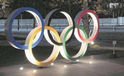 The Olympic rings are illuminated Tuesday near the New National Stadium in Tokyo.