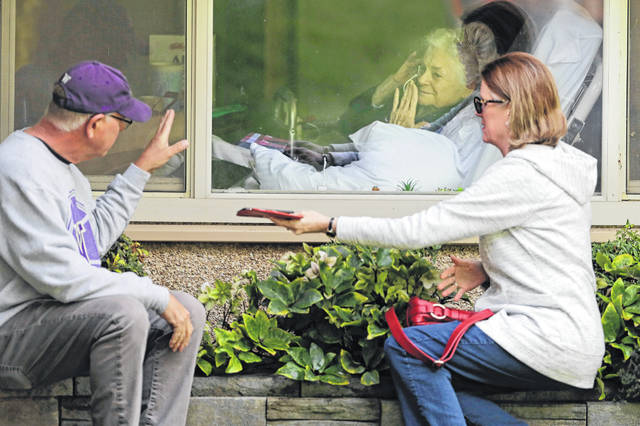 Judie Shape, center, who has tested positive for the coronavirus, blows a kiss to her son-in-law, Michael Spencer, left, as Shape's daughter, Lori Spencer, right, looks on, Wednesday, March 11, 2020, as they visit on the phone and look at each other through a window at the Life Care Center in Kirkland, Wash., near Seattle. In-person visits are not allowed at the nursing home. The vast majority of people recover from the new coronavirus. According to the World Health Organization, most people recover in about two to six weeks, depending on the severity of the illness.