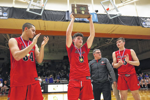 Shawnee's Tyson Elwer, left,, John Barker, and George Mangas accept the Division II district championship trophy the Indians won Saturday night at Ohio Northern University in Ada.