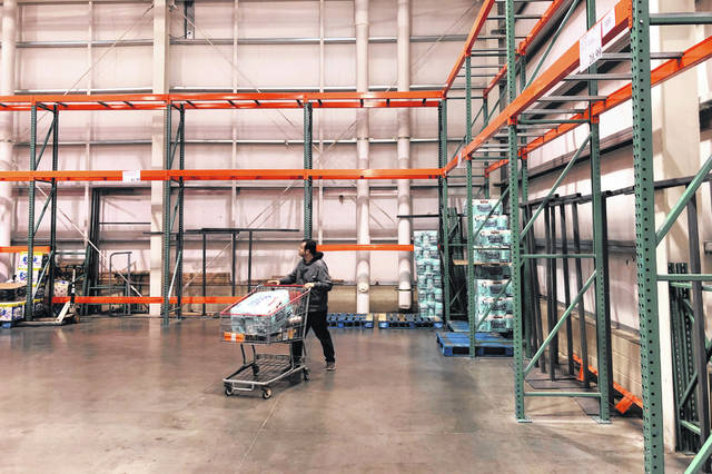 FILE - In this March 2, 2020 file photo, a customer walks past mostly empty shelves that normally hold toilet paper and paper towels at a Costco store in Teterboro, N.J. Legions of nervous hoarders are stocking up on canned goods, frozen dinners, toilet paper, and cleaning products.