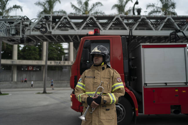 Firefighter Elielson Silva arrives to play his trumpet from the top of a ladder for residents cooped up at home, during a lockdown to help contain the spread of the new coronavirus in Rio de Janeiro, Brazil, Sunday, April 5, 2020. On Sunday, he played in three separate neighborhoods, always sporting his heavy, fire-resistant jacket and fire helmet despite temperatures above 80 degrees Fahrenheit. (AP Photo/Leo Correa)
