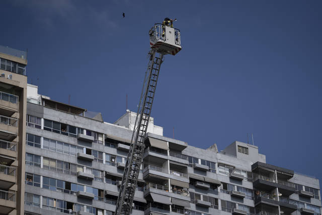 """Firefighter Elielson Silva plays his trumpet on the top of a ladder for residents cooped up at home, during a lockdown to help contain the spread of the new coronavirus in Rio de Janeiro, Brazil, Sunday, April 5, 2020. As he played in several Rio neighborhoods on Sunday, his final numbers were Brazil's national anthem, then """"Hallelujah."""" (AP Photo/Leo Correa)"""