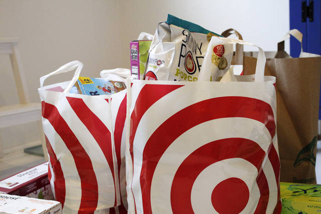 In this Sunday, March 29, 2020, photo, groceries loaded in plastic bags are seen after a shopping trip in Portland, Ore. Just weeks earlier, cities and even states across the U.S. were busy banning straws, limiting takeout containers and mandating that shoppers bring reusable bags or pay a small fee. Grocery clerks are nervous that the virus could linger on reusable fabric bags and their unions are backing them up with demands to end plastic bag fees and suspend bag bans. The plastics industry has seized the moment, lobbying to overturn existing bans on single-use plastics. (AP Photo/Gillian Flaccus)