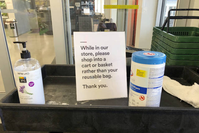 In this Sunday, March 29, 2020, photo, a sign posted at an entrance to a 365 Whole Foods store advises customers not to use their own bags while shopping in Lake Oswego, Ore. Just weeks earlier, cities and even states across the U.S. were busy banning straws, limiting takeout containers and mandating that shoppers bring reusable bags or pay a small fee. Grocery clerks are nervous that the virus could linger on reusable fabric bags and their unions are backing them up with demands to end plastic bag fees and suspend bag bans. The plastics industry has seized the moment, lobbying to overturn existing bans on single-use plastics. (AP Photo/Gillian Flaccus)
