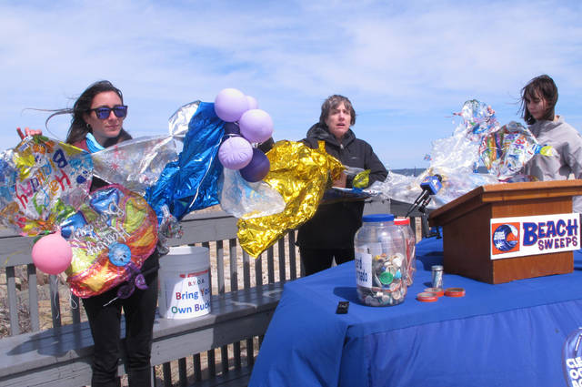In this April 2, 2019 photo, Lisa Cordova, left, Cindy Zipf, center and Alison McCarthy, right, of the Clean Ocean Action environmental group, unfurl a banner made of balloons they picked up from the beach at Sandy Hook N.J. during a news conference.  Figures released on Tuesday, April 14, show that volunteers from the group removed nearly half a million items of trash from New Jersey's beaches in 2019. (AP Photo/Wayne Parry)