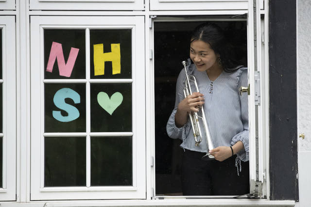 "National Youth Orchestra of Great Britain trumpet player Tian Hsu, 16, gives a dedication for a video her family was recording just before taking part in a socially distanced orchestra performance of Beethoven's ""Ode to Joy"" from a window of her home in south west London, during the lockdown to prevent the spread of coronavirus, Friday, April 17, 2020. The members of the National Youth Orchestra, took part in the coordinated Ode to Joy-a-thon on Friday, each giving their own 40 second performance, with photos or videos taken by their families to share on social media. They dedicated the performance to the National Health Service staff, key workers, and people who feel isolated in their homes during the lockdown. (AP Photo/Matt Dunham)"