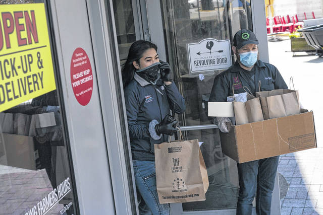 Employees wearing protective gloves and masks, walk to-go orders to waiting cars at Founding Farmers restaurant in Potomac, Md., on Wednesday. Founding Farmers is closed to in-restaurant dining during the coronavirus outbreak, and its owners are considering how the industry will chain when people can dine in their restaurants again.
