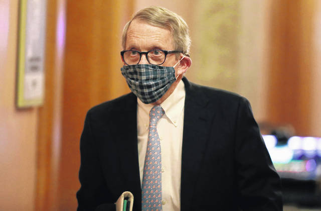 Wearing his protective mask made by his wife, Ohio Gov. Mike DeWine walks into his daily coronavirus news conference Thursday at the Ohio Statehouse in Columbus.