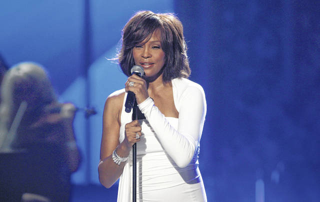 "In this Nov. 22, 2009 file photo, Whitney Houston performs at the 37th Annual American Music Awards in Los Angeles. A feature film about Houston's life is in the works from Anthony McCarten, the screenwriter of ""Bohemian Rhapsody."""