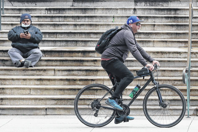 A man checks his phone as a man rides bicycle on the sidewalk in downtown Chicago, Wednesday, April 22, 2020. Illinois Gov. Jay Pritzker said the state could reopen in stages, with each region facing different restrictions amid the COVID-19 pandemic.
