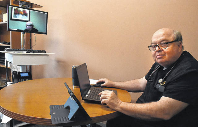 Chief Clinical Officer Dr. Warren Morris of Health Partners of Western Ohio practices telemedicine at his office in Lima.