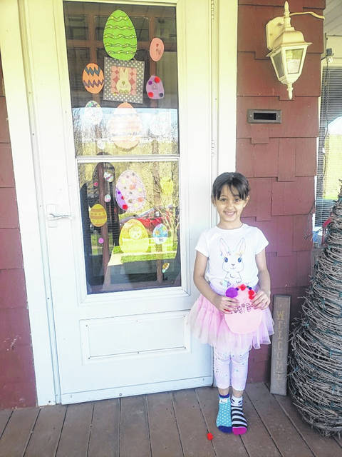 Rylee Williams, 6, of Lima, and her family show off their decorated Easter eggs for the community-wide egg hunt.