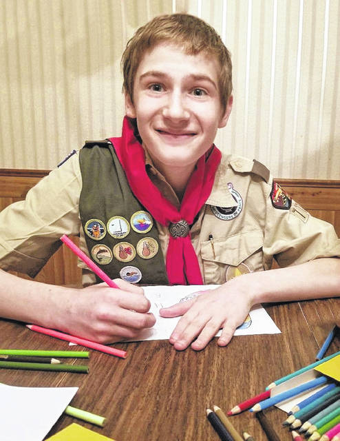 Jackson Weber, a Tenderfoot Scout with Troop 777, works on making greeting cards for local seniors.