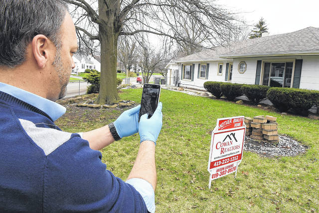 Using his cell phone, Jason Liening of Cowan Realtors, demonstrates how he performs a virtual tour of a home at 1402 Ellison Drive in Lima.