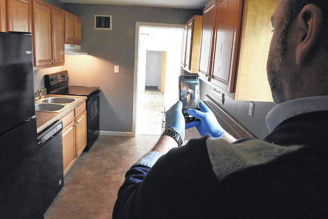 Using his cell phone, Jason Liening of Cowan Realtors shows the kitchen of a house on the market.
