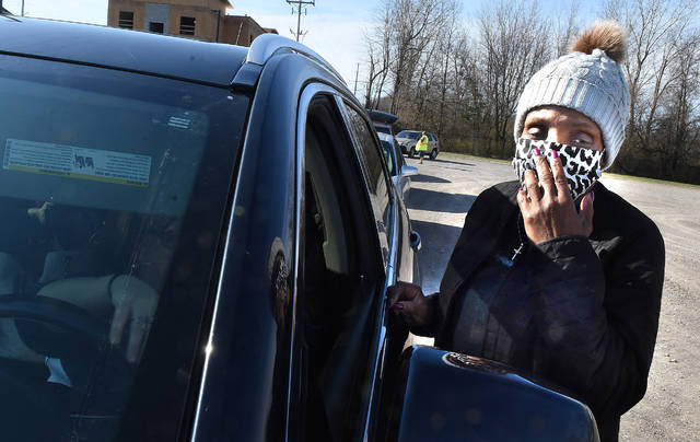 Rose Dillard, of Lima, wears a homemade mask while talking with her daughter-in-law waiting in line at the West Ohio Food Bank fresh produce distribution.