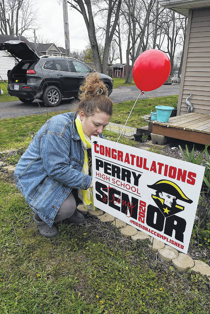 Melissa Pepple, a faculty member at Perry High School, ties a balloon to a congratulations yard sign delivered by teachers and parents in a caravan on Wednesday.