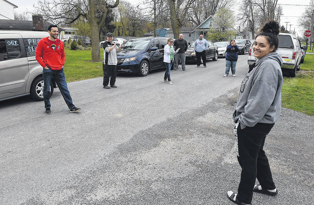 Perry High School senior Caitland Boroff, 17, talks to teachers and parents after a caravan delivered a congratulations yard sign to her home Wednesday. Some area schools have worked out special ways to recognize their seniors, who aren't enjoying the traditional wrapup of their educational careers with the coronavirus pandemic closing school buildings.