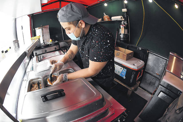 Christian Montenegro makes a taco while working inside the Taco Movil food truck.