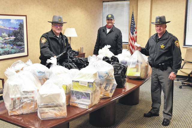 Auglaize County Sheriff Allen Solomon, Ohio Attorney General Dave Yost and Union County Sheriff Jamie Patton stand with personal protective equipment being donated to first responders.