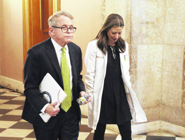 Ohio Gov. Mike DeWine and Ohio Department of Health Director Dr. Amy Acton leave one of the daily coronavirus news conferences at the Statehouse. [Doral Chenoweth/Dispatch]