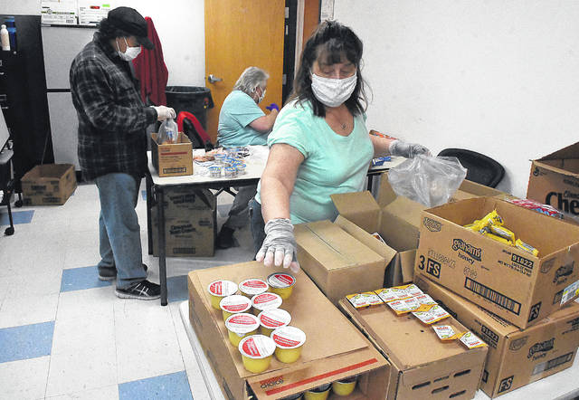 West Ohio Community Action Partnership employees, from left, Kim Upshaw, Jenny Slife and Jeannie Luchini pack lunches for children in the region on Tuesday mornings. WOCAP packs up to 250 lunches which are delivered on Wednesday and Thursday by bus. The coronavirus pandemic increased the amount of free food distributed in the region.