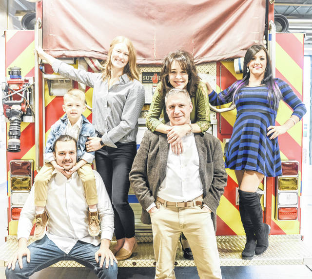 The Corwin family huddles around a fire truck at the Lima Fire Department. They are, from left, Michael Corwin and son, Lochlan; Michael's fiance, Kate Bailey; Doug Corwin, Genean Corwin and Elise Corwin.