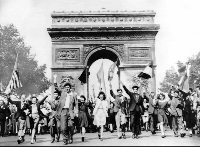 In this May 8, 1945, file photo Parisians march through the Arc de Triomphe jubilantly waving flags of the Allied Nations as they celebrate the end of World War II in Europe. Nazi commanders signed their surrender to Allied forces in a French schoolhouse 75 years ago this week, ending World War II in Europe and the Holocaust. (AP Photo, File)