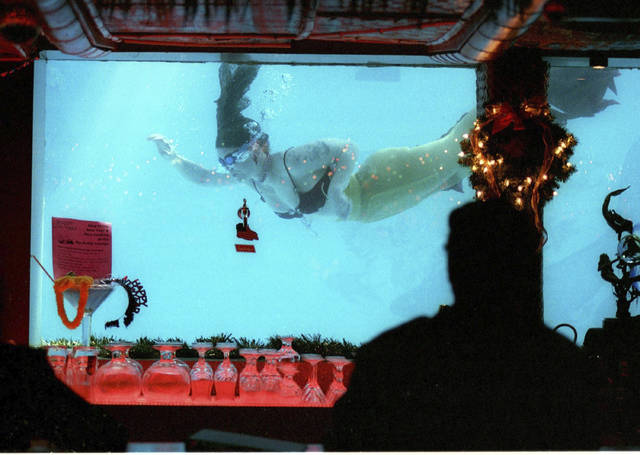 This 2012 file photo shows a woman dressed as a mermaid swimming in the pool through a window of the Sip N' Dip Lounge in Great Falls, Mont. The mermaids were scheduled to go back to work on Wednesday, May 6, 2020, after the Montana governor's office clarified that hotel pools are included in his directive to ease coronavirus restrictions. (Larry Beckner/Great Falls Tribune via AP, File)